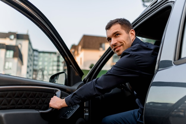 Un Bel Homme Regarde De Sa Voiture Et Regarde En Arrière. Le Chauffeur Est Dans Un Quartier Résidentiel De La Ville Photo Premium
