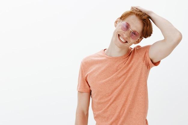 Bel Homme Rousse Insouciant Profitant De L'été, Portant Des Lunettes De Soleil Et Souriant Photo gratuit