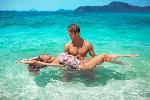 Un bel homme et sa petite amie nagent dans la mer turquoise. paradis vacances îles tropicales. Photo Premium