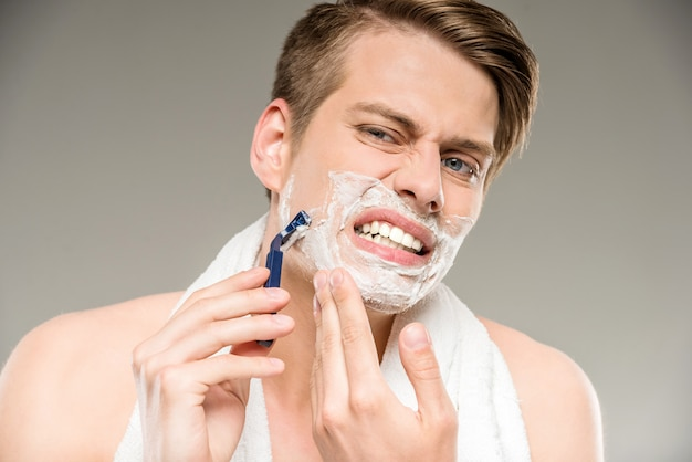Bel homme avec une serviette sur les épaules rasage après le bain. Photo Premium