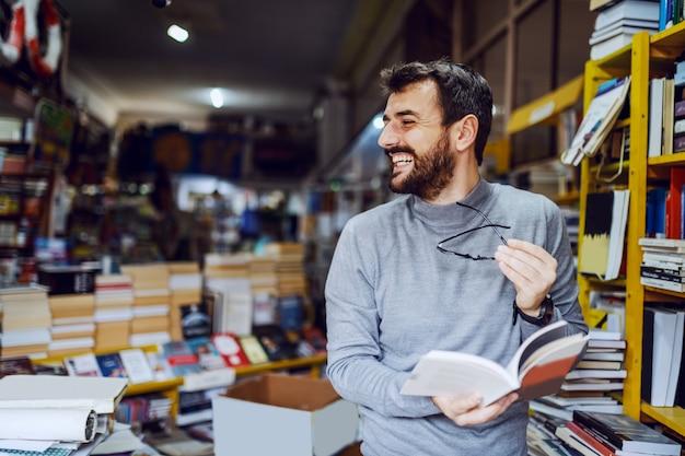 Bel Homme Souriant Caucasien Debout Dans La Librairie Avec Livre Dans Les Mains Et En Détournant Les Yeux. Photo Premium