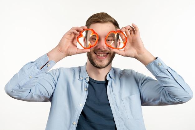 Bel homme souriant, regardant à travers deux tranches de poivron rouge Photo gratuit