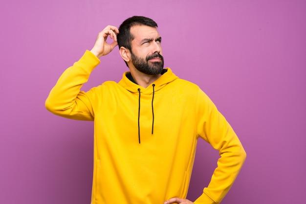 Bel homme avec un sweat-shirt jaune ayant des doutes tout en se grattant la tête Photo Premium
