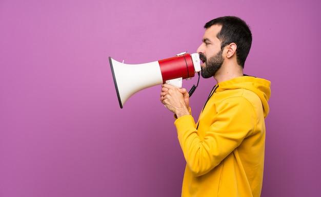 Bel homme avec sweat-shirt jaune criant à travers un mégaphone Photo Premium