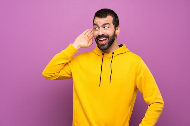 Bel homme avec sweat-shirt jaune écouter quelque chose en mettant la main sur l'oreille Photo Premium