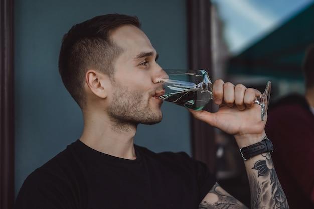 Le bel homme tatoué sur une terrasse d'été dans un café de la ville boit du vin. street cafe. Photo gratuit
