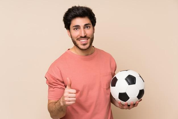 Bel homme tenant un ballon de foot Photo Premium