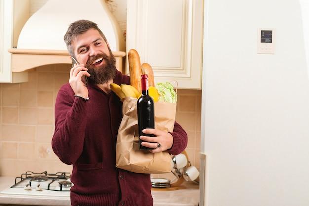 Bel Homme Tenant Un Sac En Papier Plein D'épicerie Fraîche à La Maison. Homme Barbu Avec Botte De Vin. Photo Premium