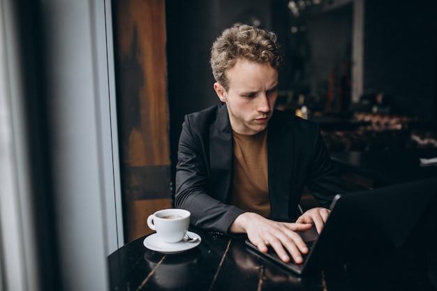 Bel homme travaillant sur un ordinateur dans un café et boire un café Photo gratuit
