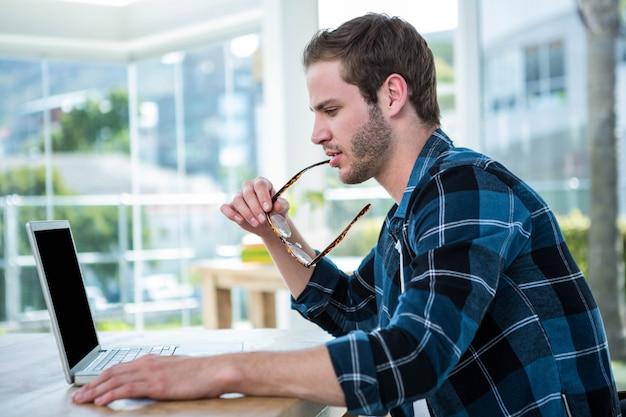 Bel homme travaillant sur ordinateur portable dans un bureau lumineux Photo Premium