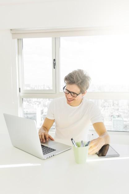 Bel homme travaillant sur ordinateur portable à la maison Photo gratuit