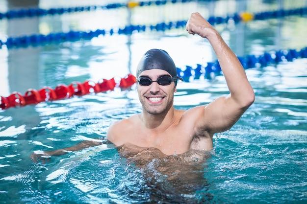 Bel homme triomphant à bras levé dans la piscine Photo Premium