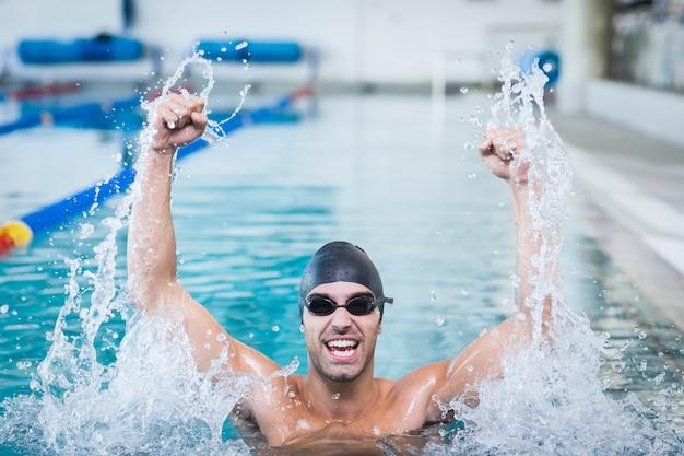 Bel homme triomphant avec les bras levés dans la piscine Photo Premium