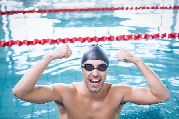 Bel homme triomphant dans l'eau à la piscine Photo Premium