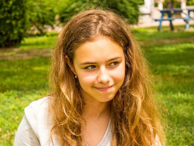 Belle adolescente aux cheveux longs souriant dans le parc sur l'herbe verte Photo Premium