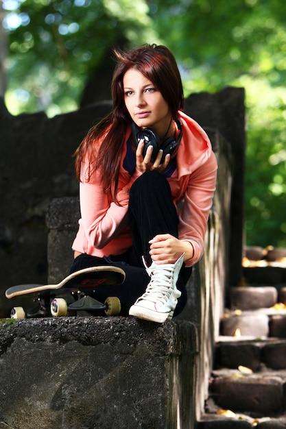 Belle Adolescente Avec Un Casque Dans Le Parc Photo gratuit