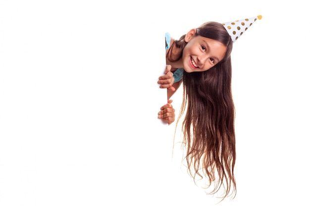 Belle Adolescente Heureuse Avec Des Cheveux Longs Portant Un Chapeau De Papier Festif à La Recherche De Panneau D'affichage Avec Copie Espace Photo Premium