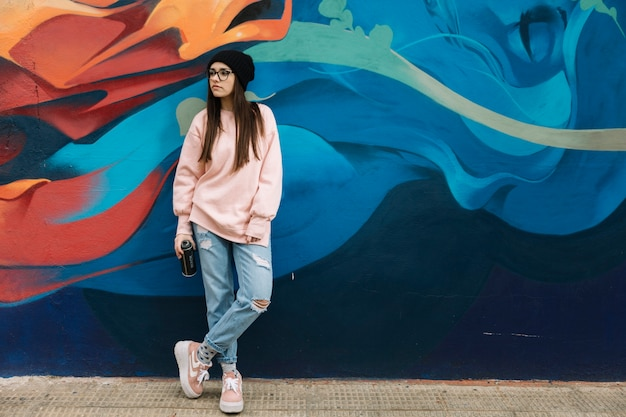 Belle aérosol de tenue de jeune femme debout devant le mur de graffitis colorés Photo gratuit