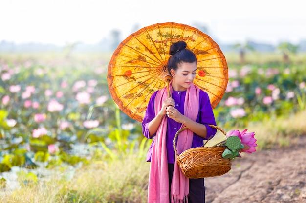 Belle agricultrice thaïlandaise vêtue d'une robe traditionnelle thaïlandaise et promenade sur le lac de lotus Photo Premium