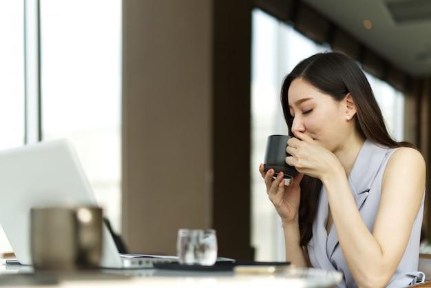 Belle asiatique belle fille parle un repos en buvant une tasse de café assis dans un café. Photo Premium