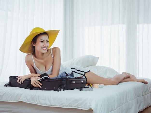 Belle asiatique préparant des sacs pour partir en vacances Photo Premium