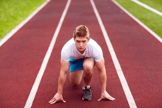 Belle athlète sur une piste de course est prêt à courir Photo Premium