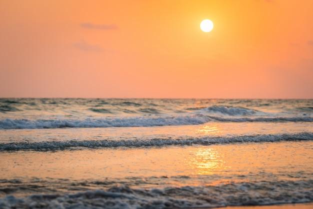 Belle aube avec coucher de soleil et belle plage, vague douce et claire sur la plage de sable fin Photo Premium