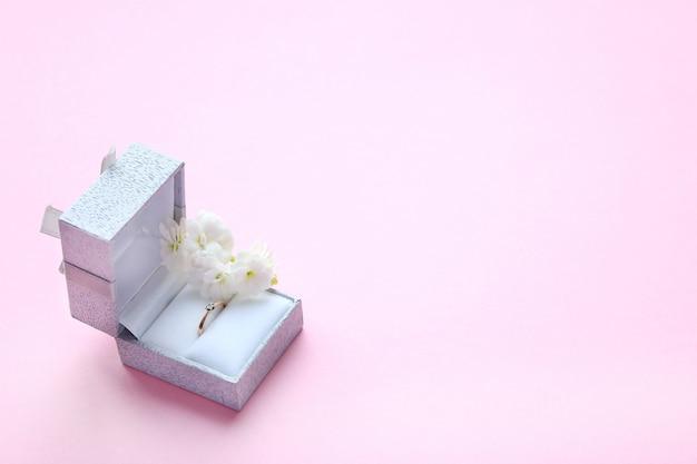 Belle bague de fiançailles en or brillant avec pierre précieuse diamant dans une boîte grise et des fleurs blanches sur fond rose Photo Premium