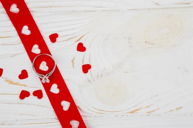 Belle bague sur ruban près des coeurs d'ornement Photo gratuit