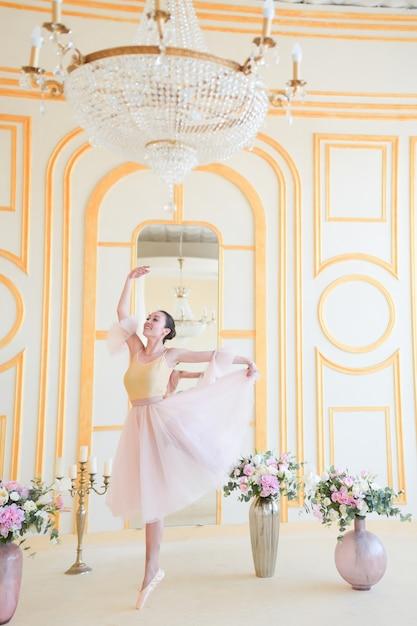 Belle ballerine en vêtements roses pose dans une chambre de luxe Photo gratuit