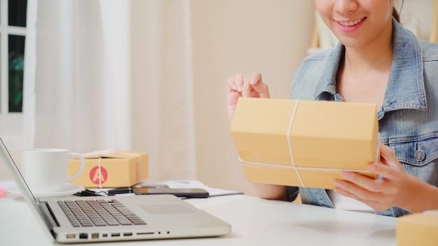 Belle belle asiatique jeune entrepreneur femme d'affaires propriétaire d'une pme en ligne vérifiant le produit en stock et l'enregistrant à l'ordinateur travaillant à la maison. Photo gratuit