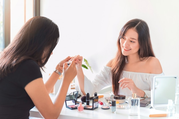 Belle Blogueuse Asiatique Montrant Comment Vernir Les Ongles Et Utiliser Des Produits Cosmétiques. Photo Premium