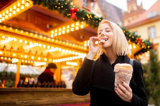 Belle blonde avec un gâteau à la broche au marché de noël à wroclaw, en pologne Photo Premium