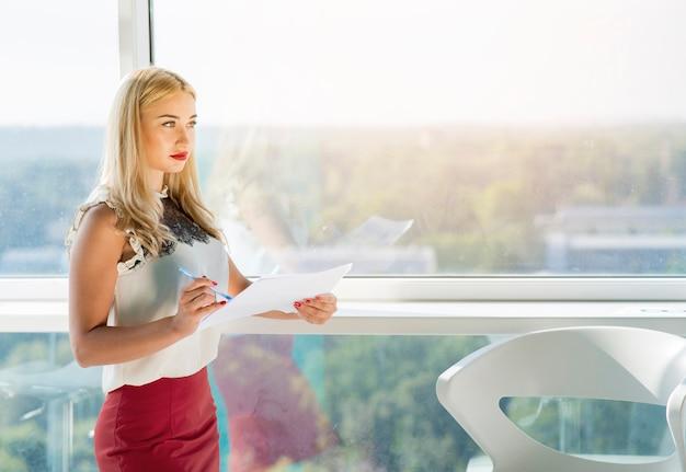 Belle blonde jeune femme debout près de la vitre porte document Photo gratuit