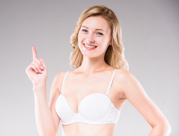 Belle blonde en soutien-gorge décontracté blanc en regardant la caméra. Photo Premium
