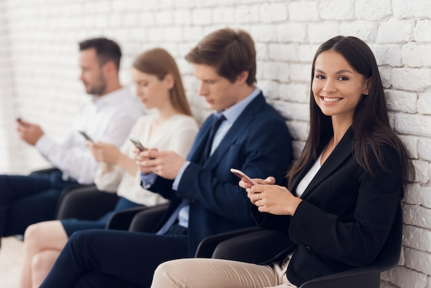 Belle brune assise à la réception avec smartphone. Photo Premium