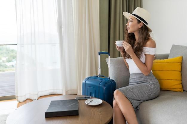 Belle brune aux cheveux bouclés est assise sur un canapé au chapeau clair et pose avec une valise et une tasse de café en regardant par la fenêtre Photo Premium