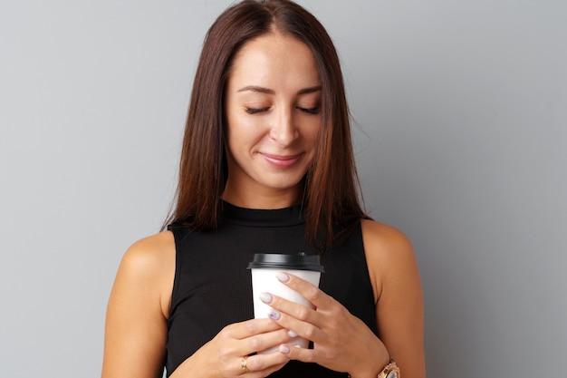 Belle brune jeune femme tenant une tasse de café Photo Premium