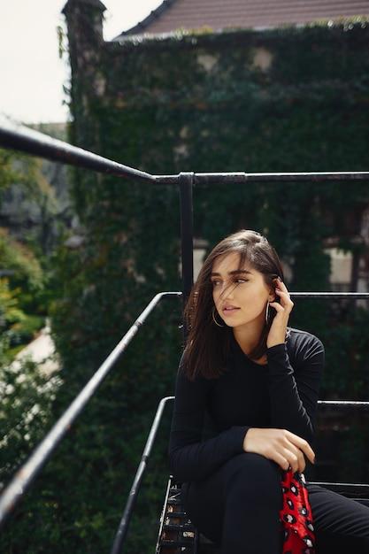 Belle brune posant sur un escalier noir Photo gratuit