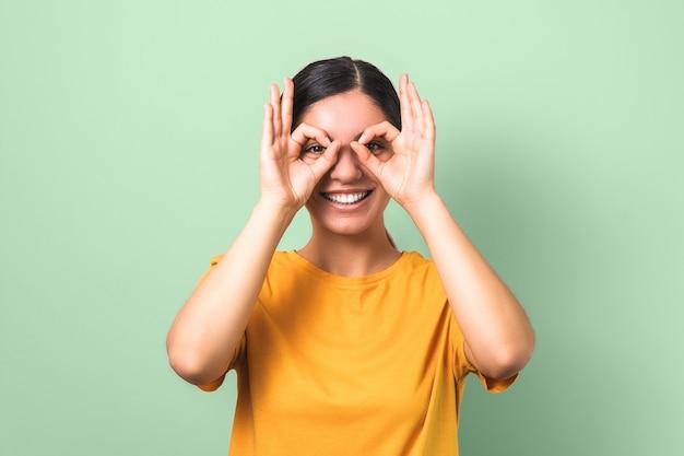 Belle Brune En T-shirt Jaune Faisant Des Lunettes De Ses Doigts Et Drôle De Visage Souriant Sur Fond Vert Photo Premium