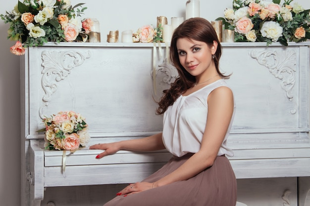 Belle charmante brune dans la maison, vieux piano Photo Premium