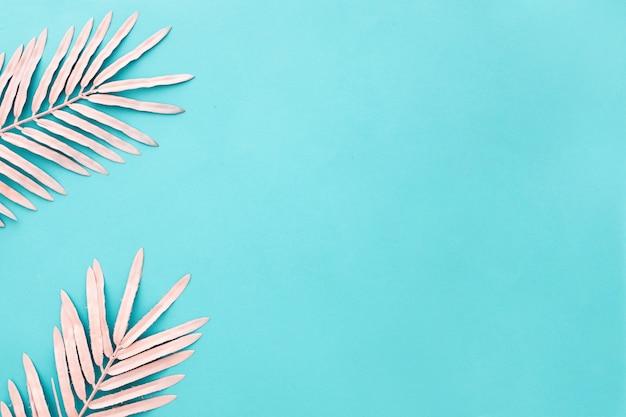 Belle composition avec des feuilles de palmier rose sur bleu clair avec fond Photo gratuit