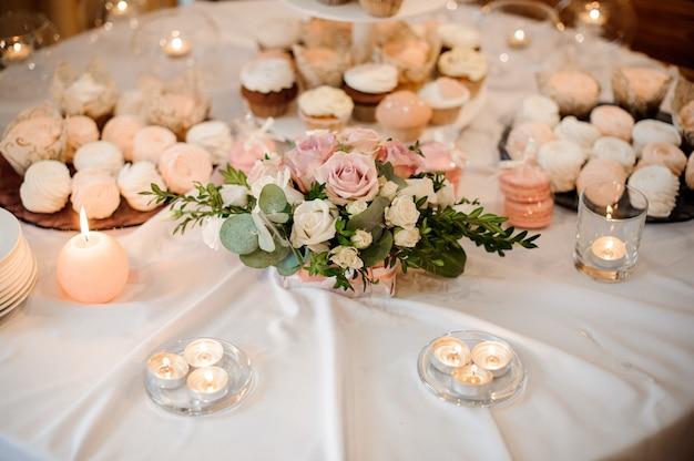 Belle composition florale et bougies décorant une table de fête servie avec des gâteaux Photo Premium