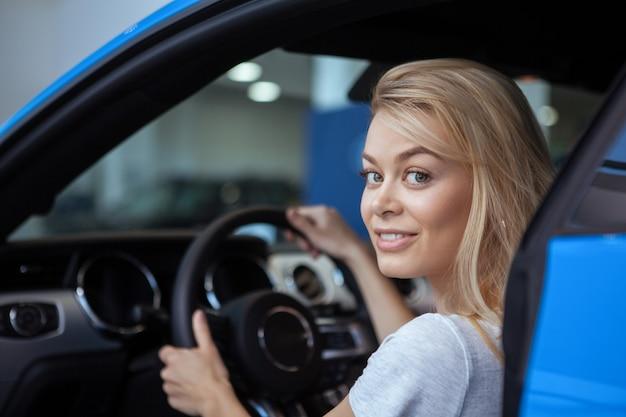 Belle conductrice sourit à la caméra avec ses mains sur le volant d'une nouvelle automobile Photo Premium