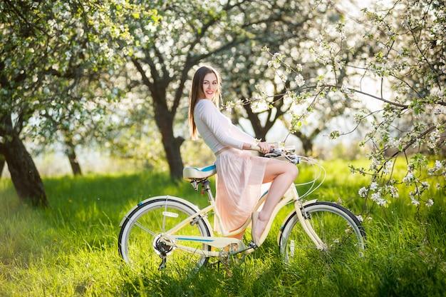 Belle cycliste avec vélo rétro dans le jardin de printemps Photo Premium