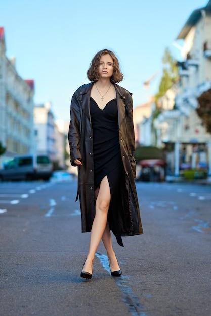Belle dame en long manteau vintage et robe de soirée au milieu de la route tôt le matin Photo Premium