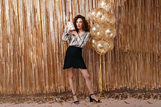 Belle Dame En Tenue De Fête Tenant Un Cadeau Sur Fond De Ballons Dorés Photo gratuit