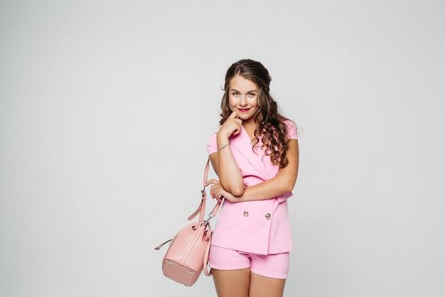 Belle et élégante femme vêtue d'un costume rose posant au studio. Photo Premium