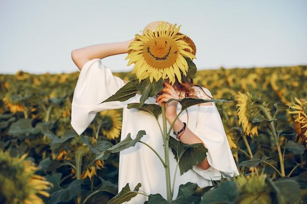 Belle et élégante fille dans un champ de tournesols Photo gratuit