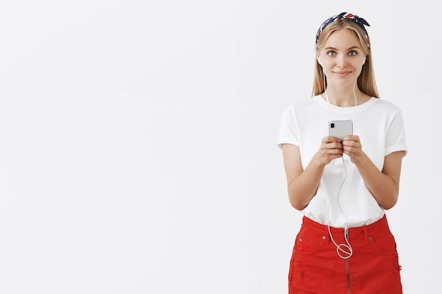 Belle élégante Jeune Fille Blonde Posant Contre Le Mur Blanc Photo gratuit